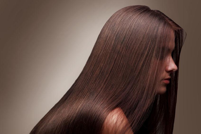 Mulher de cabelos castanhos longos, lisos e brilhantes de perfil em frente a um fundo vinho