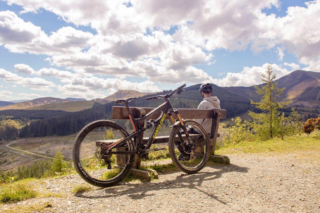 Imagem mostra um rapaz de capacete sentado num banco de madeira, olhando, da encosta de um morro, os relevos da paisagem. A sua bicicleta está apoiada no mesmo banco, atrás do rapaz.