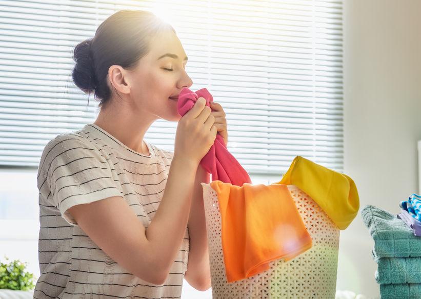 Mulher cheirando roupa.