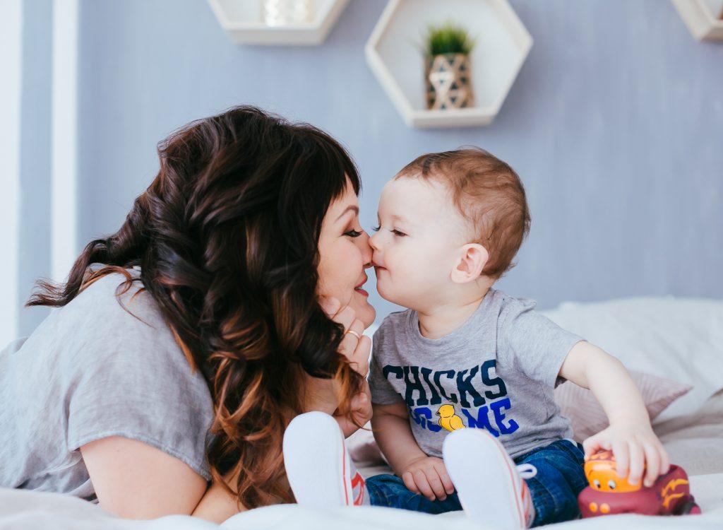 Imagem com uma mãe olhando para o filho bebê sentado na cama e usando camiseta, calça jeans e tênis.