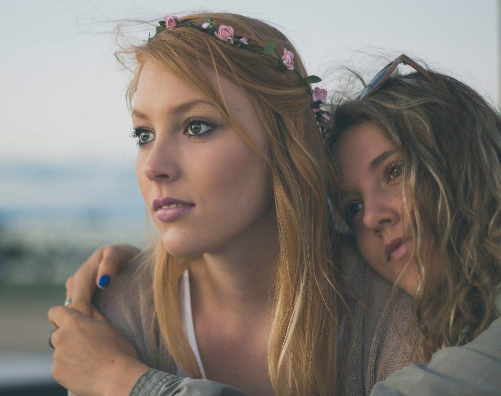 Mulher com tiara de flores e amiga ao lado.