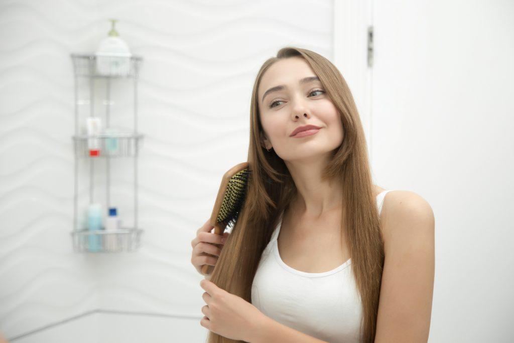 Mulher de cabelos castanhos se penteia em um banheiro branco.