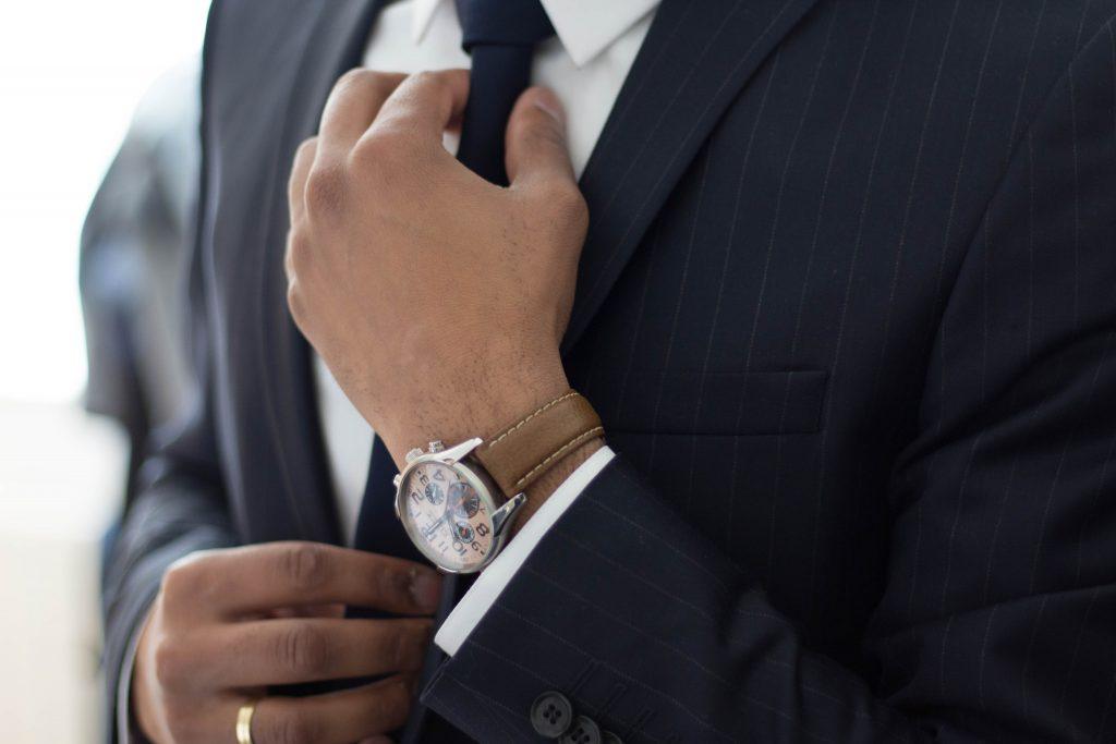 Imagem de um homem usando um relógio com pulseira de couro.