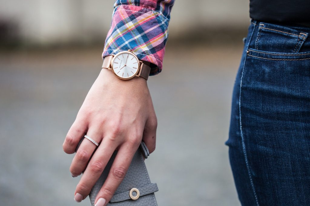 Imagem de uma moça usando um relógio.