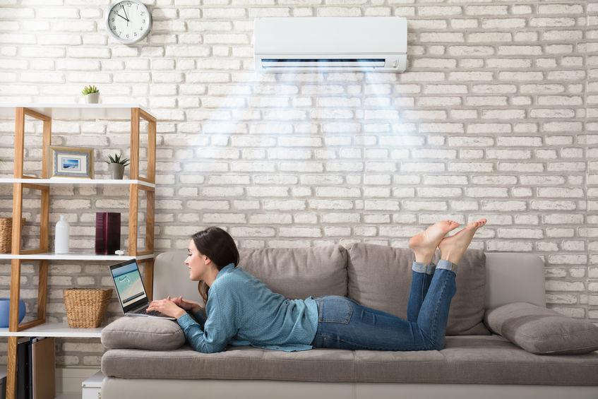 Mulher deitada no sofá, usando notebook, com o ar condicionado ligado acima dela.