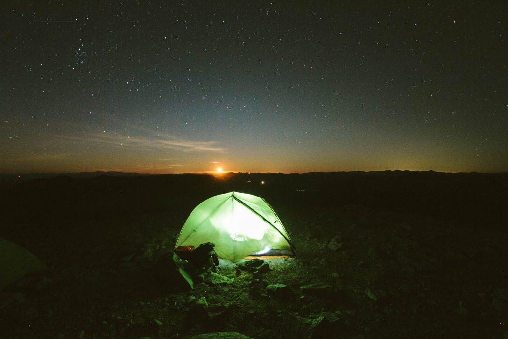 Imagem mostra uma barraca montada sobre um terreno rochoso, iluminada por dentro. Ao fundo, o sol se põe.