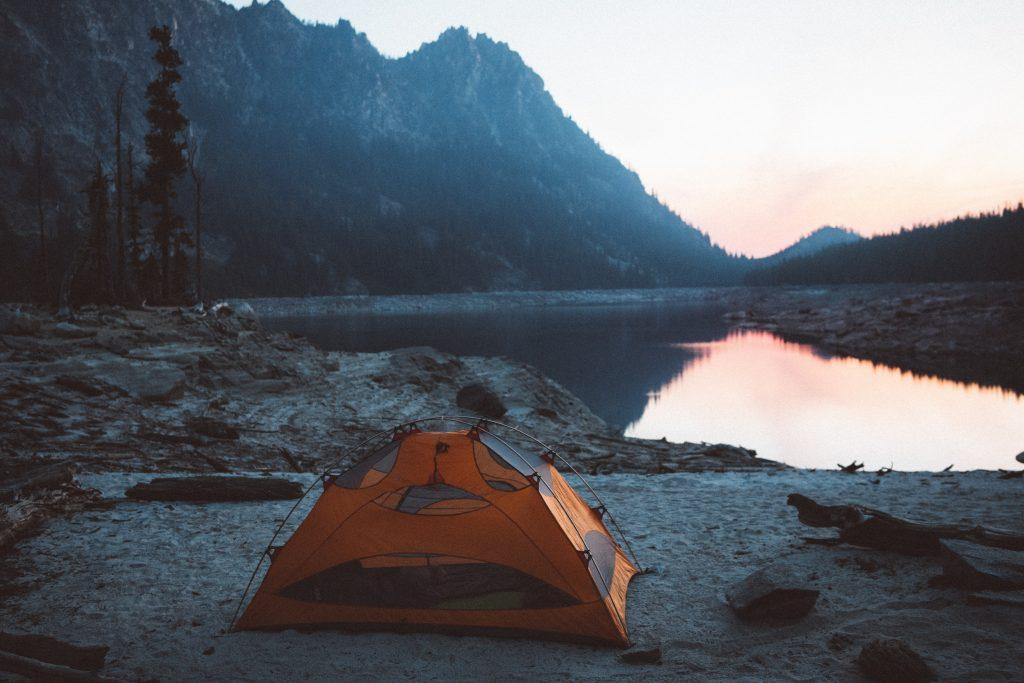 Imagem mostra uma barraca compacta montada na beira de um lago.