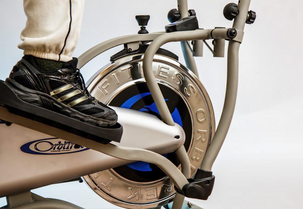 Imagem mostra o close de um pé no pedal de uma bicicleta ergométrica, focando nas estrutura da parte inferior da máquina.
