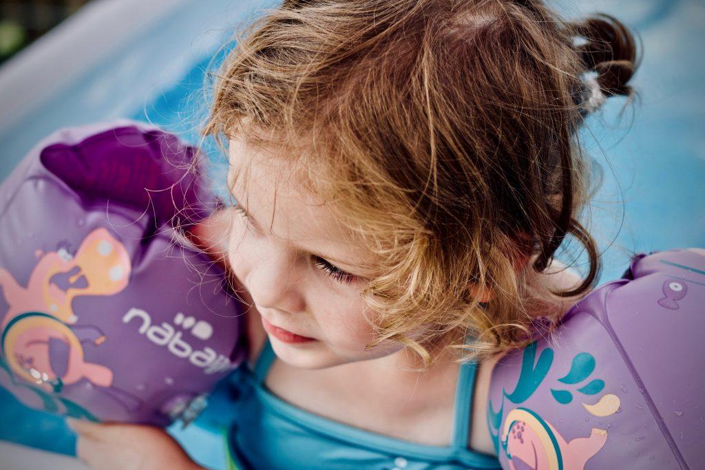 Na foto uma menina dentro de uma piscina usando boias de braço.