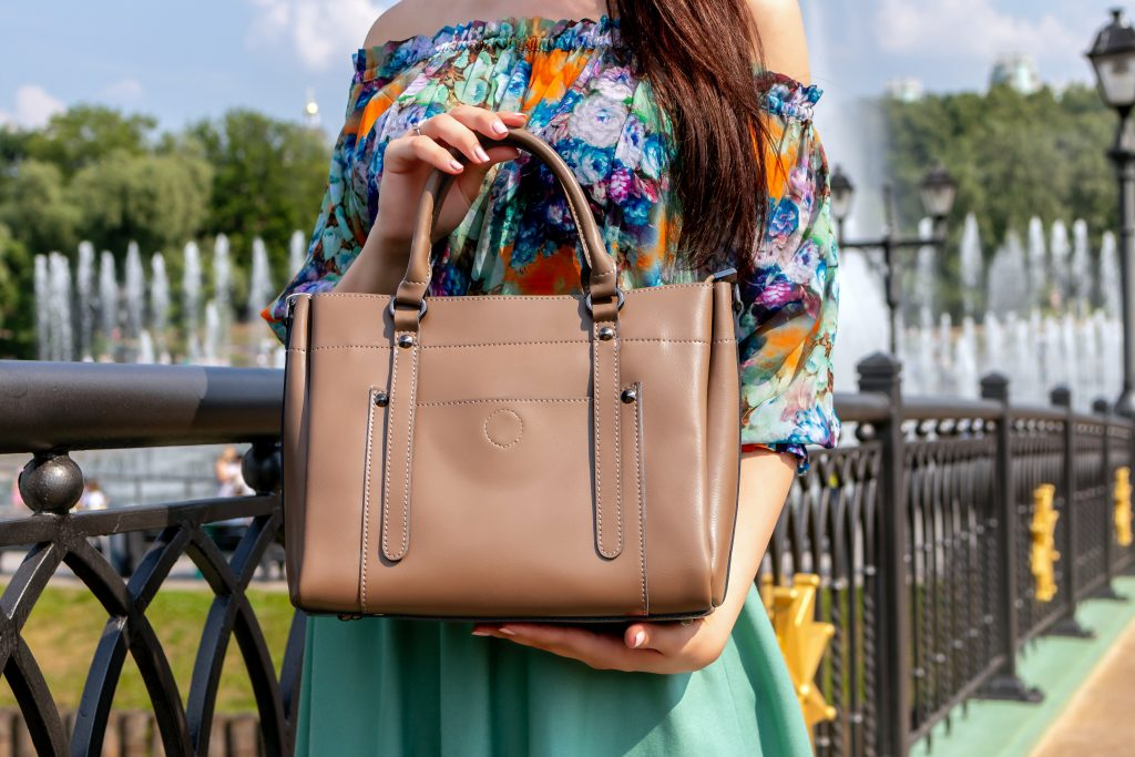 Imagem de uma mulher segurando uma bolsa.