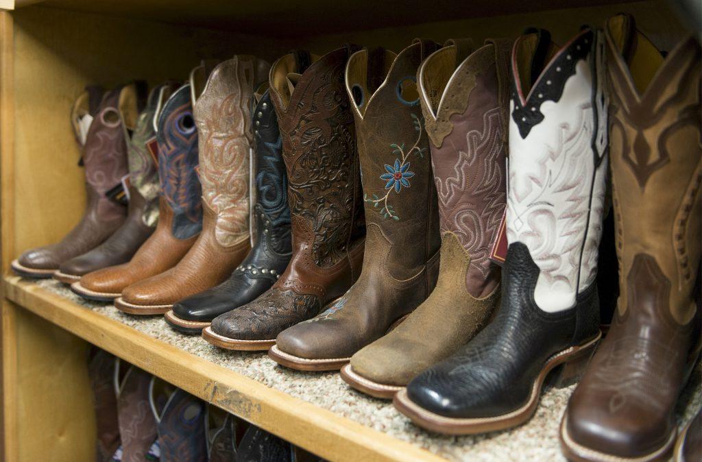 Imagem mostra uma prateleira com diversas botas texanas masculinas.