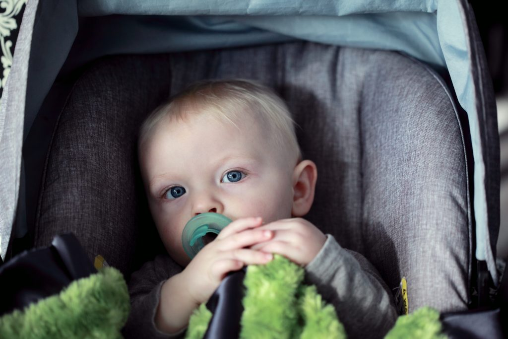 Menino em um carrinho de bebê chupando bico e segurando um paninho.