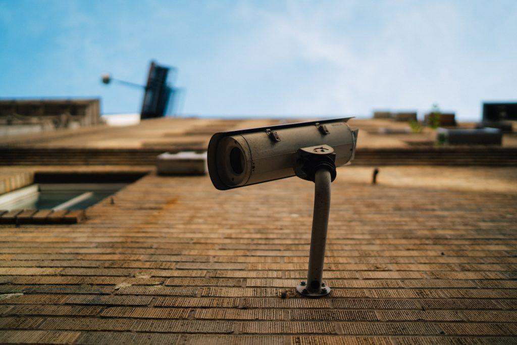 Imagem mostra uma câmera de monitoramento em uma área externa.