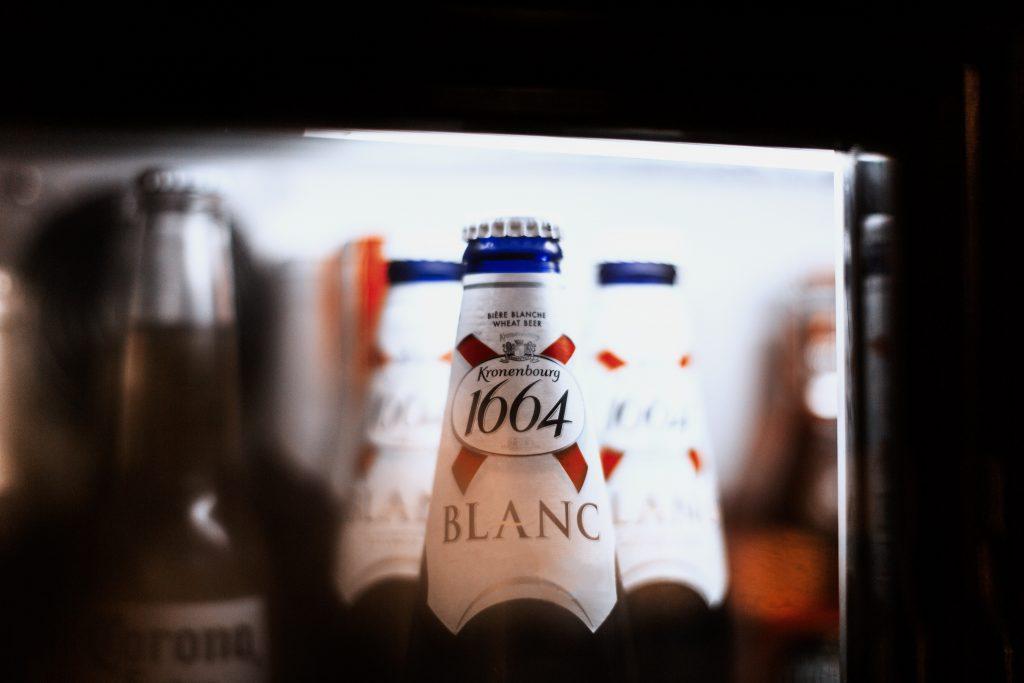 Imagem mostra o close do gargalo de uma garrafa de cerveja, tampada e com selo. A garrafa é emoldurada pelos limites da porta do refrigerador em que está inserida.
