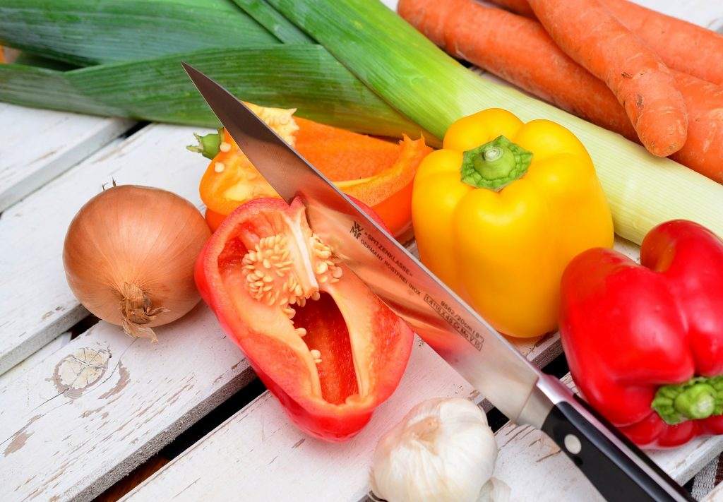 Imagem de faca cortando e legumes cortados