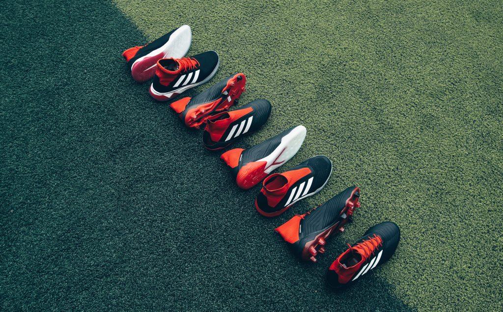 Imagem mostra uma fileira de chuteiras Adidas, próprias para diversas superfícies, sobre uma grama sintética bicolor.