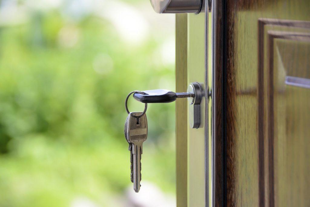 Porta de casa aberta com chave na fechadura.