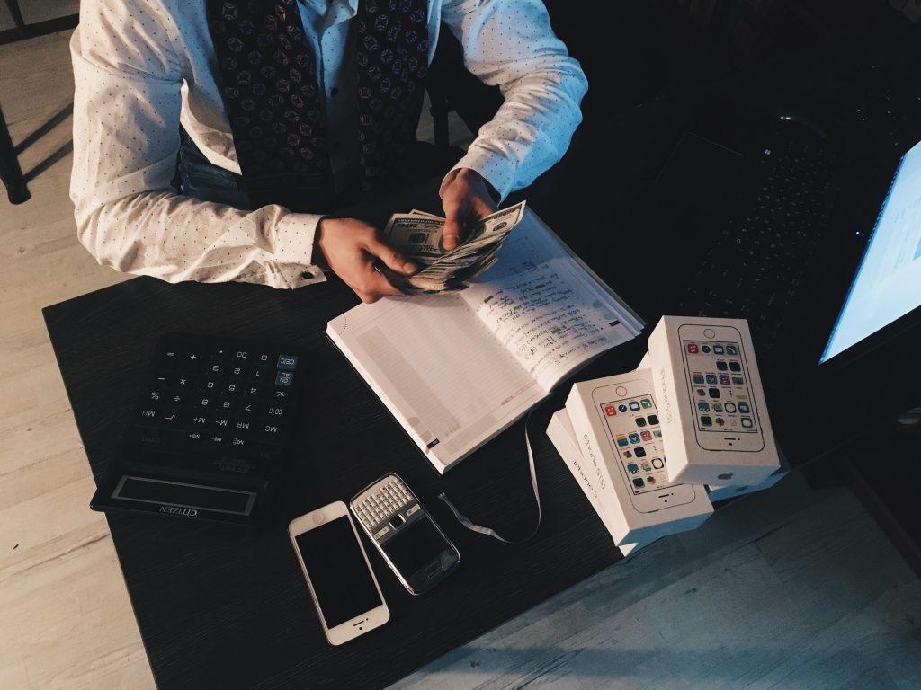 Homem com dinheiro e calculadora.