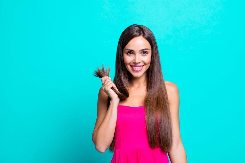 Mulher com longos cabelos castanhos se penteia com uma escova raquete de madeira.
