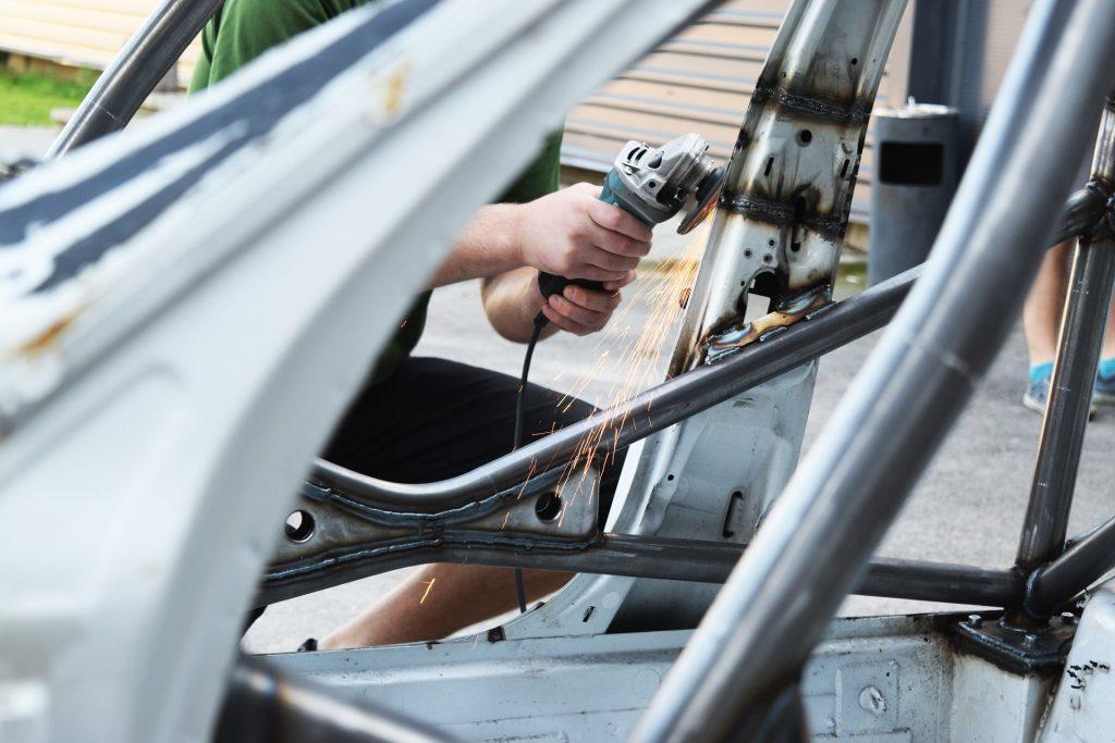 Imagem mostra uma pessoa usando uma esmerilhadeira na lataria de um automóvel.