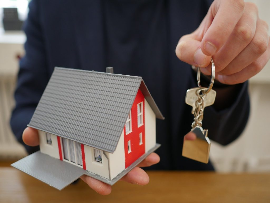 Homem entregando chaves e segurando uma réplica de casa.