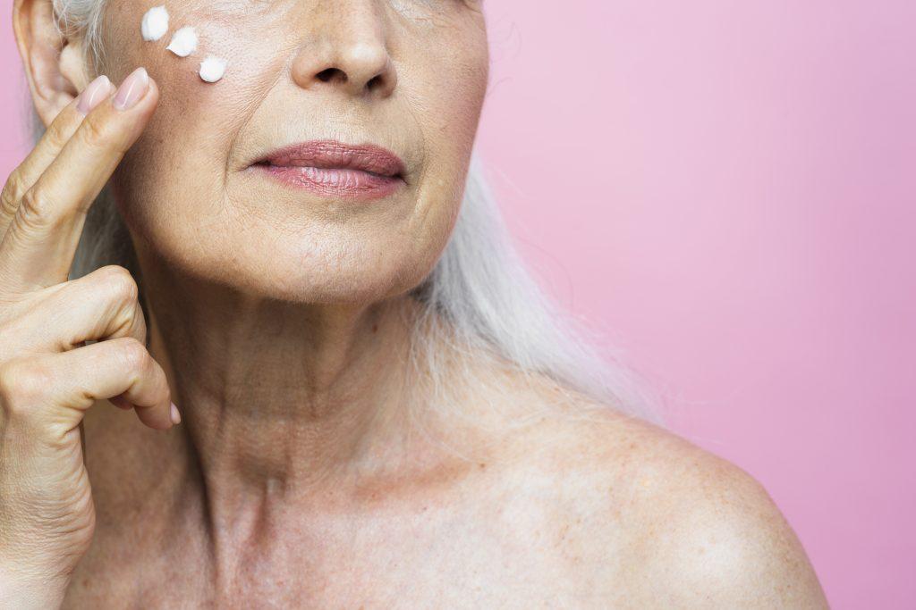 Foto mostra uma mulher mais velha. O rosto dela não aparece totalmente. Mesmo assim, ela passa hidratante na bochecha.