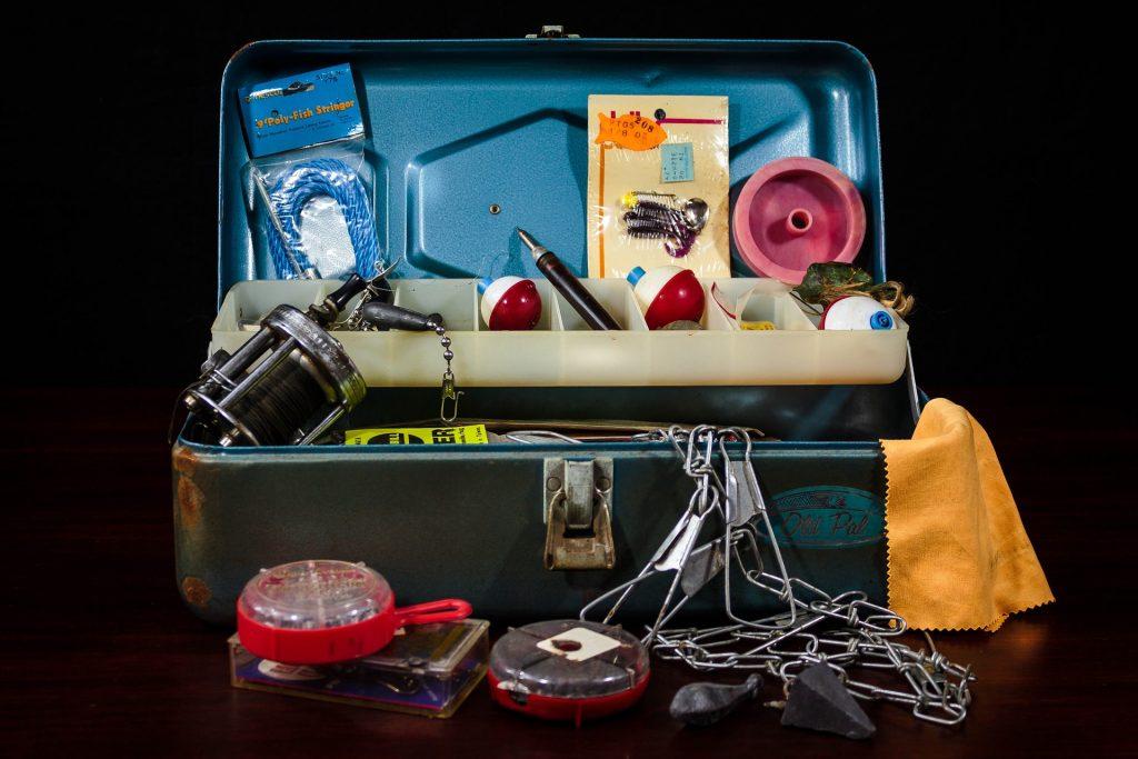 Imagem mostra uma maleta com diversos equipamentos para pesca.