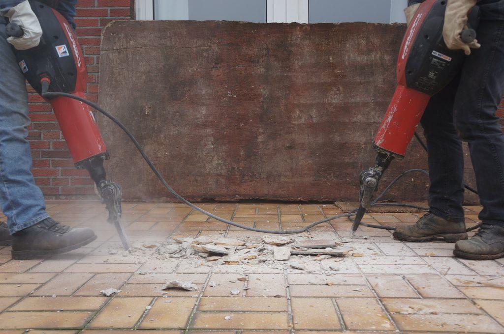 Imagem mostra duas pessoas usando marteletes no piso de um lugar.