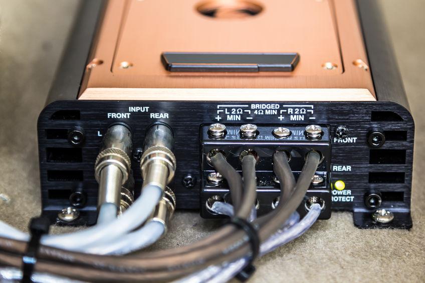 Imagem mostra um módulo amplificador sobre um fundo branco, com foco nas suas portas de conexão.