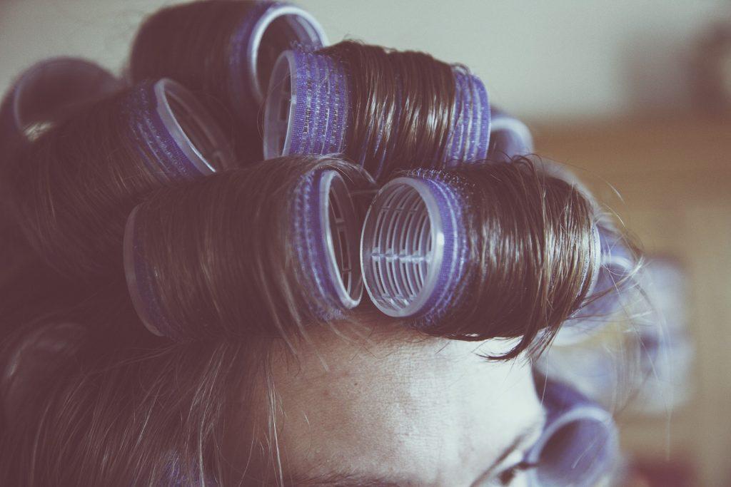 Imagem de mulher usando modeladores de cabelo para conseguir cachos