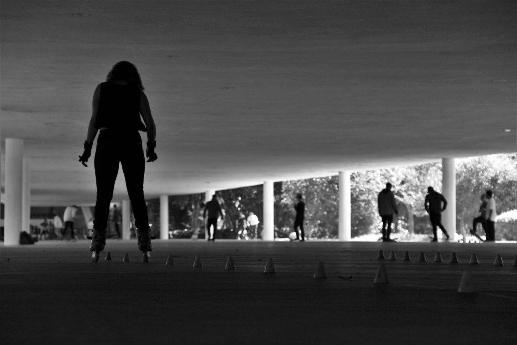 Imagem em preto e branco mostra uma mulher, sob a cobertura de um pavilhão, patinando por entre pequenos cones de treino, dispostos linearmente no chão.