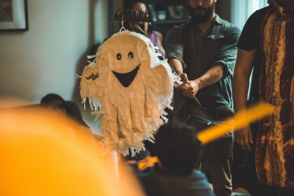 Pinhata de fantasma com crianças e adultos ao redor.
