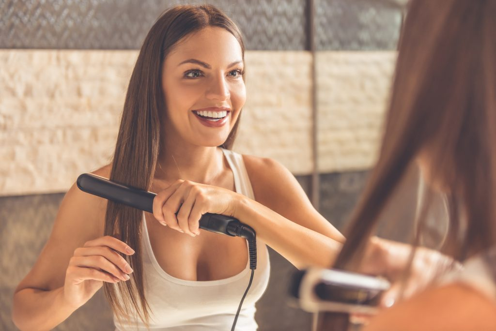 Na foto uma mulher fazendo chapinha no cabelo em frente a um espelho.