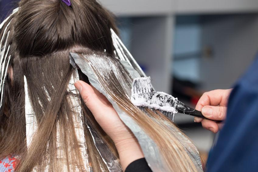 Cabeleireira aplica tintura em cabelo de uma loira sentada