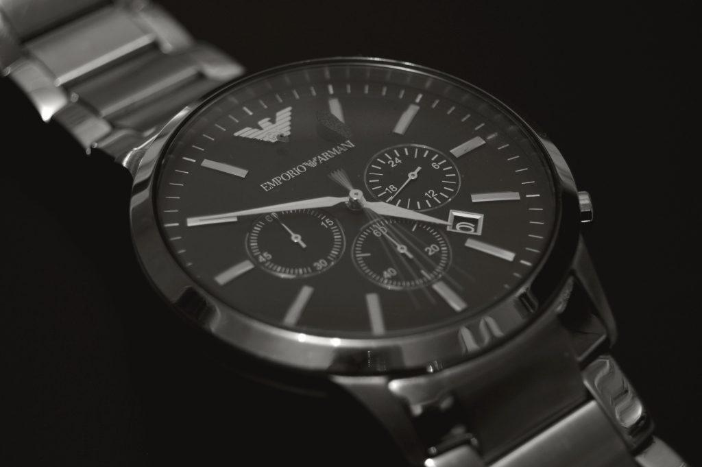 Um relógio Emporio Armani está prateado e com fundo do visor preto está em close num fundo preto.