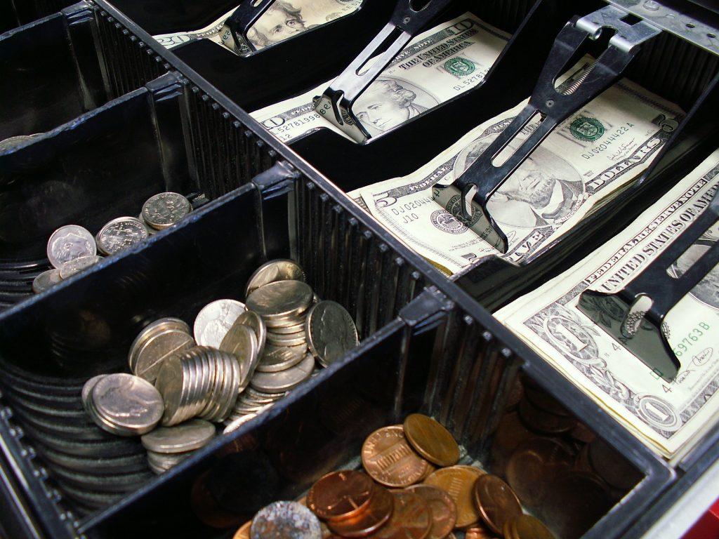 Imagem mostra uma caixa registradora cheia de dinheiro.