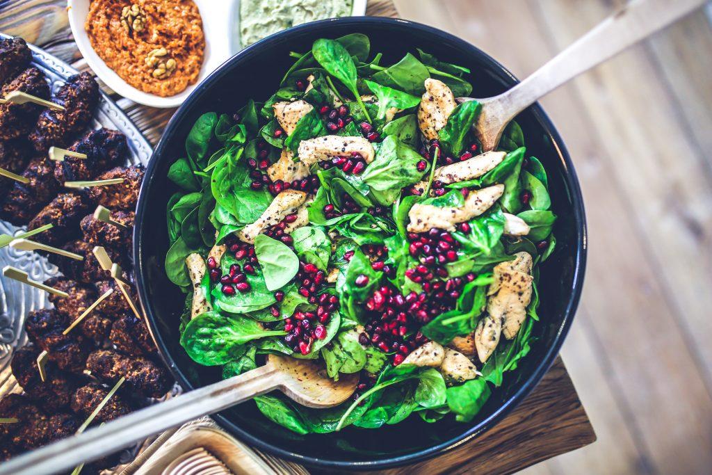 a foto um mesa com salada, carnes e outros alimentos.