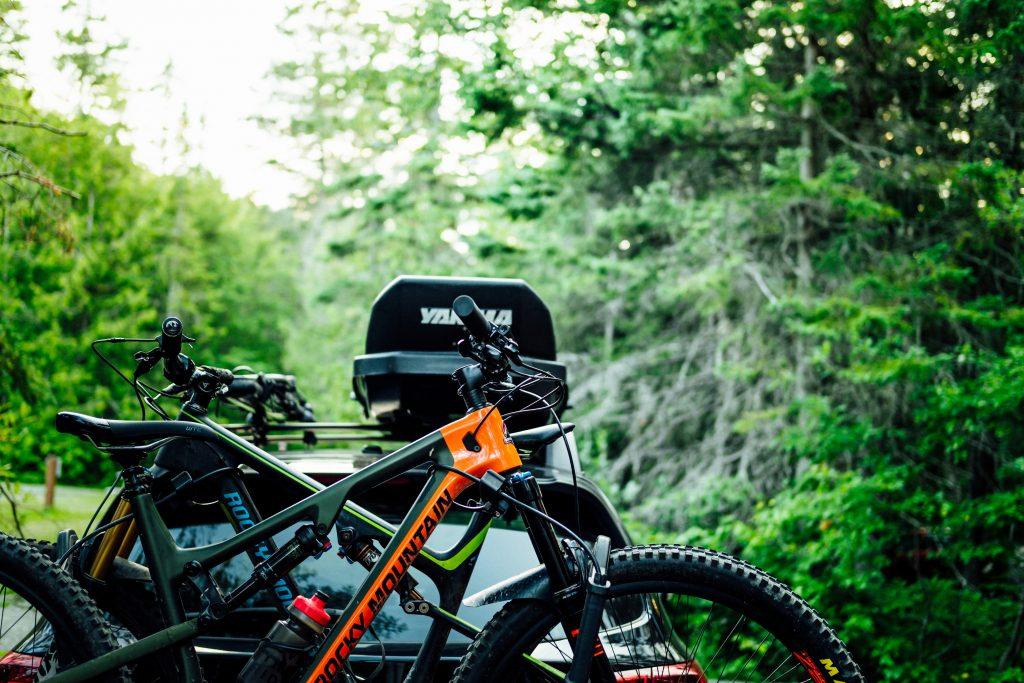 Imagem mostra, em primeiro plano, duas mountain bikes emparelhadas. Ao fundo, a traseira de um carro, desfocada.