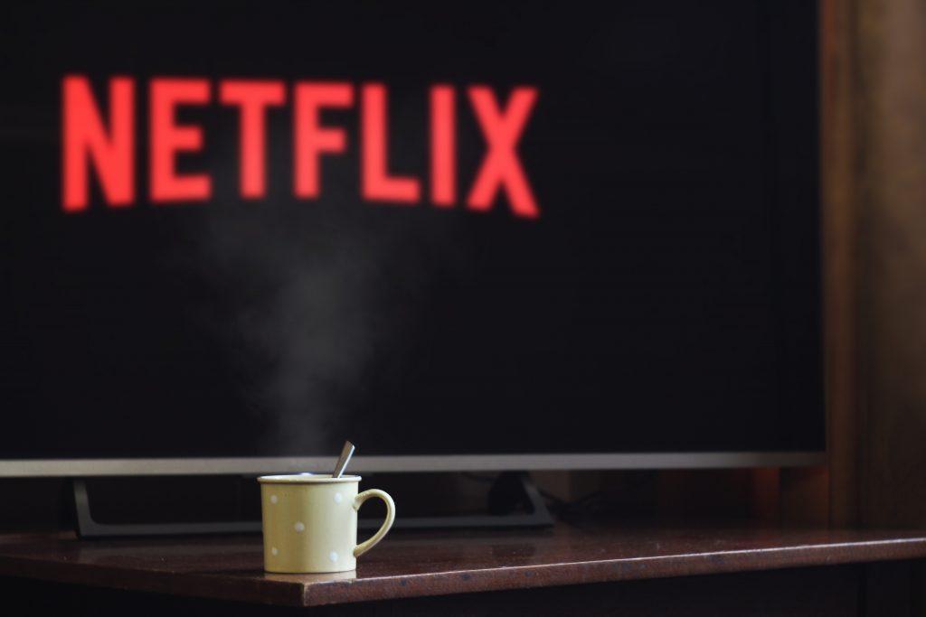 Imagem mostra uma TV ligada e mostrando o logo da Netflix.