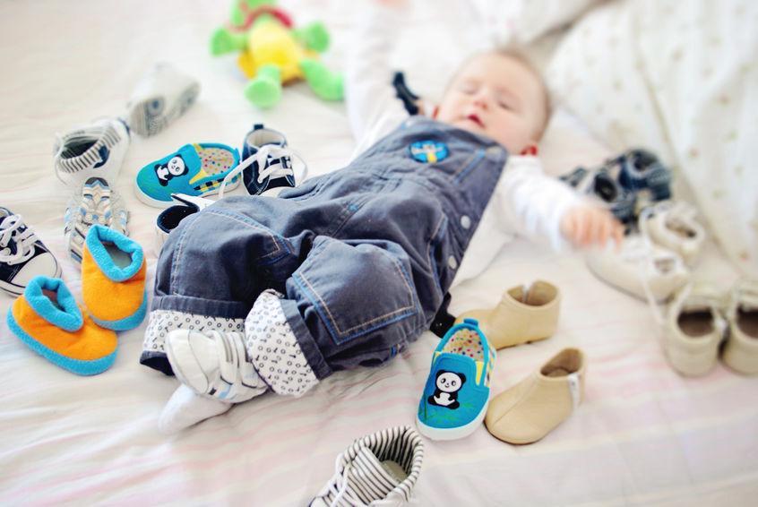 Imagem de um bebê deitado na cama, com vários sapatinhos em volta.