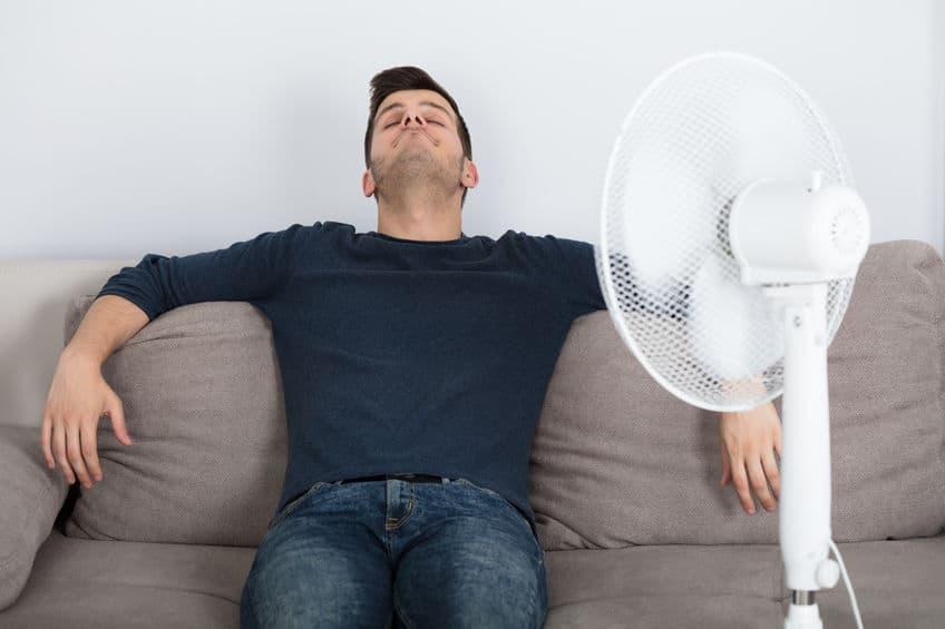 Na foto um homem sentado em um sofá em frente a um ventilador.