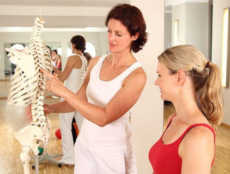 Imagem de uma mulher explicando o funcionamento da coluna vertebral para a outra.