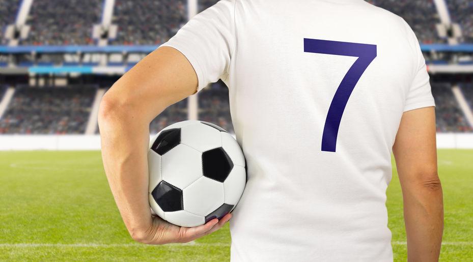 Homem com camisa de futebol, segurando bola e com estádio ao fundo.