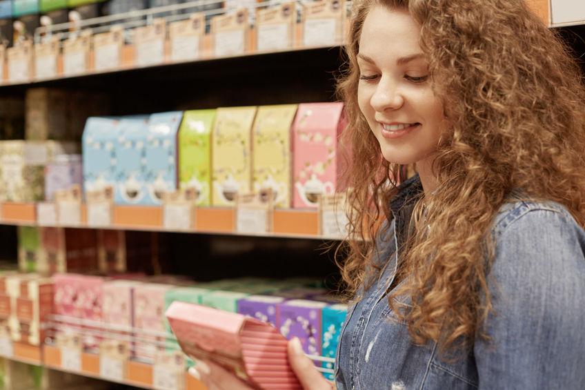 Mulher loira com cabelos presos e regata branca escolhe produtos para cabelo em uma perfumaria