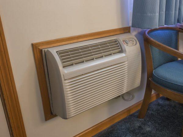 Ar condicionado de janela instalado com moldura de madeira próximo ao piso em um quarto