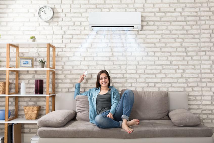 Imagem mostra mulher sentada em uma sala ligando o ar-condicionado.
