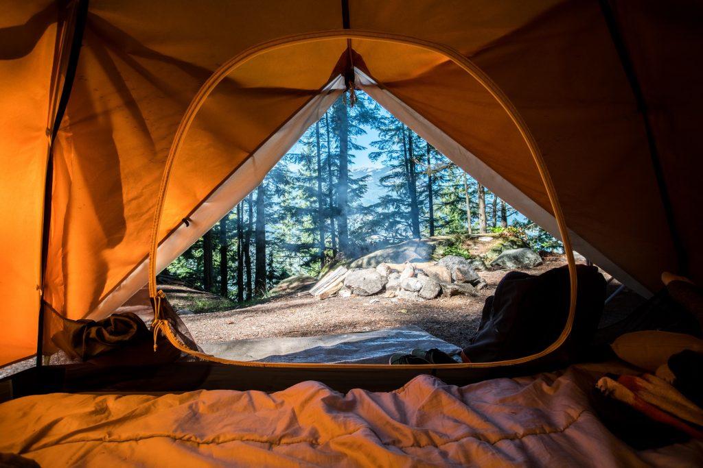Imagem mostra o interior de uma barraca com a porta aberta. No lado de fora, é possível ver árvores e um amontoado de lenha