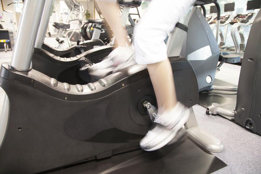 Imagem foca na parte inferior de uma bicicleta ergométrica, mostrando apenas as pernas de uma pessoa em movimento, pedalando.