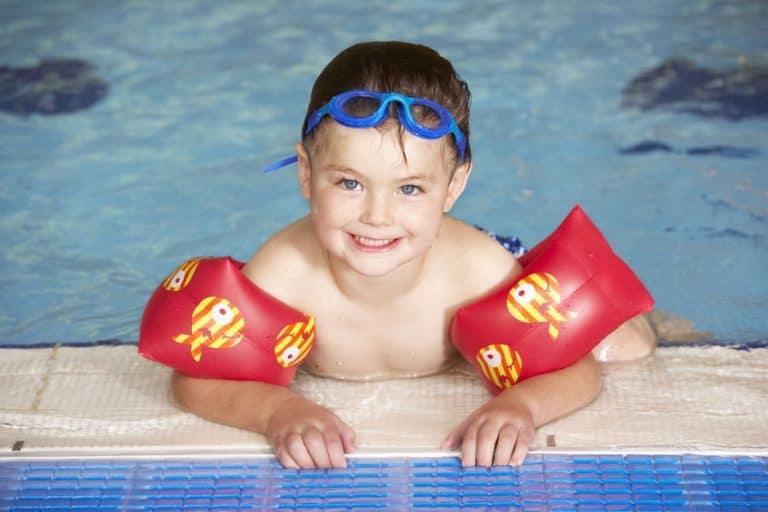 Na foto um menino na beira de uma piscina usando boias de braço.