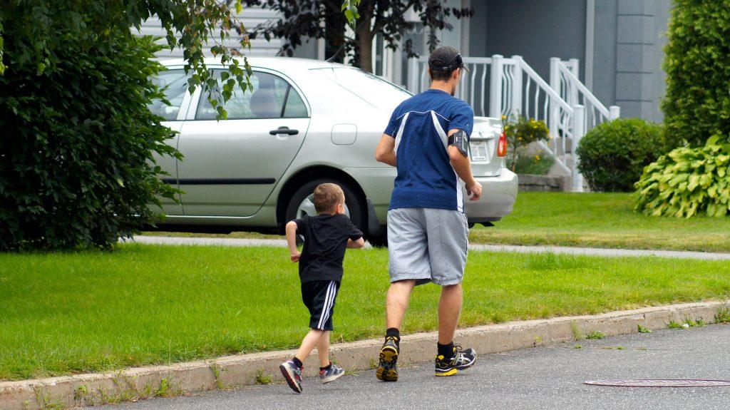 Homem e criança correndo na rua.